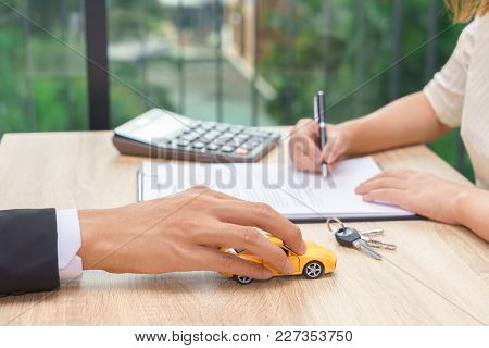 Woman Signing Car Loan Agreement Contract With Car Key And Calculator On Wooden Desk.