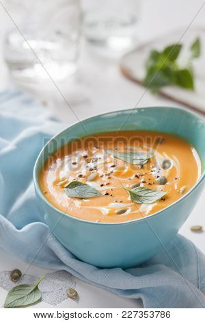 Roasted Pumpkin And Carrot Soup With Cream, Pumpkin Seeds And Basil Leaf