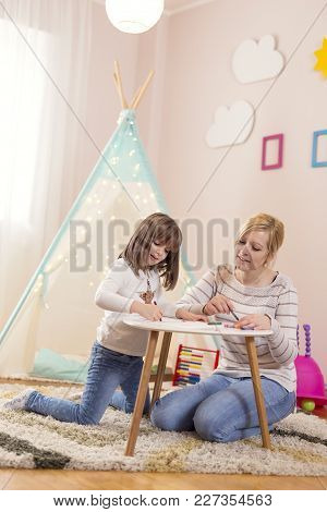 Mother And Daughter Playing In A Play Room, Drawing With Crayons