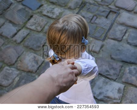 A Girl Holds Her Father's Hand