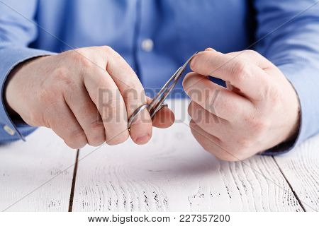 Male Do Manicure Himself On Wooden Table