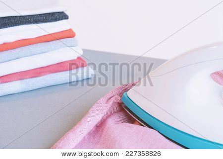 Close Up View Of Man Ironing Blue Shirt On Ironing Board With Stack Of Ironed Shirts. Housework Conc