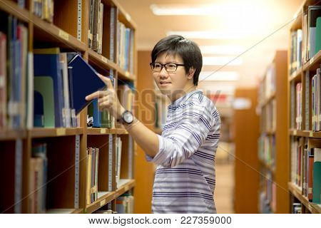 Young Asian Man University Student Choosing Book In Library, Education Research And Self Learning In