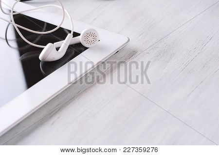 Close Up Of Tablet With Earphones On Wooden Table. Technology Concept