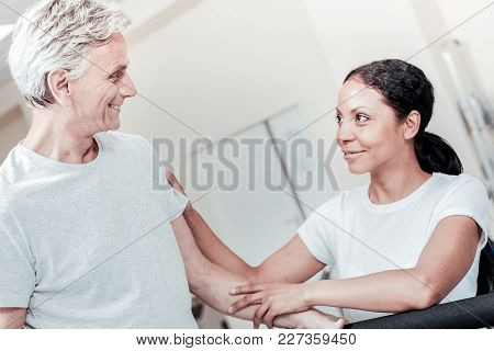 Nice Atmosphere. Inspired Energetic Old Grey-haired Man Smiling And A Cheerful Dark-haired Dark-eyed
