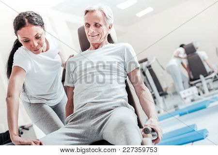 Therapist. Gleeful Determined Old Grey-haired Man Smiling And Exercising On A Training Device While