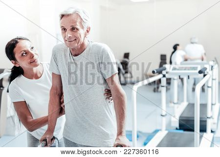 I Am Determined. Inspired Old Grey-haired Man Exercising While A Pretty Smiling Dark-haired Dark-eye