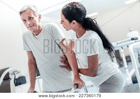 Being Active. Joyful Concentrated Old Grey-haired Man Exercising While A Pretty Dark-haired Afro-ame