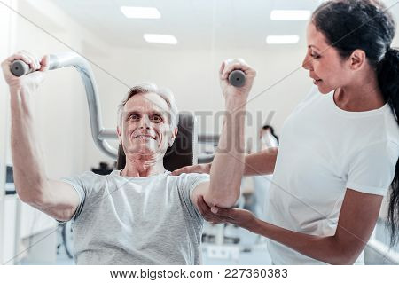 Doing My Best. Exuberant Energetic Old Grey-haired Man Exercising On A Training Device And A Pretty