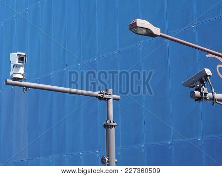 Cctv Security Surveillance  In The City. Surveillance Up High Near Street Lighting, With Blue Tarpau