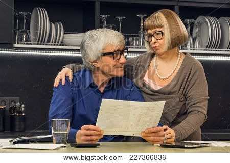Senior Couple Calculate Their Bills On Kitchen