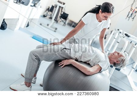 Helping While Exercising. Exuberant Old Wrinkled Grey-haired Man Lying On A Ball For Exercises And A