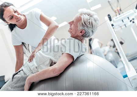 My Favourite Trainer. Exuberant Old Wrinkled Grey-haired Man Lying On A Ball For Exercises And A Joy