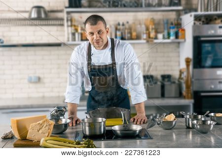Friendly Cook Is Situating In Airy Kitchen. Chef Preparing To Cook Ravioli