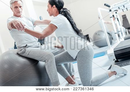 Exercises. Concentrated Old Grey-haired Man Sitting On A Ball For Exercises And A Young Smiling Dark