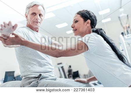 Do Like This. Concentrated Old Grey-haired Man Sitting On A Ball For Exercises And A Beautiful Young