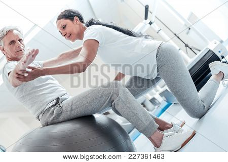 Therapeutic Potency. Concentrated Old Grey-haired Man Sitting On A Ball For Exercises And A Beautifu