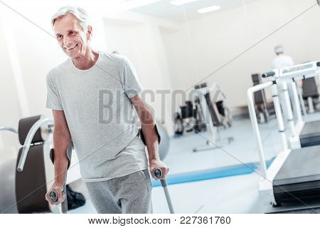 On Cloud Nine. Alert Old Grey-haired Man Smiling And Standing While Holding And Standing With The He