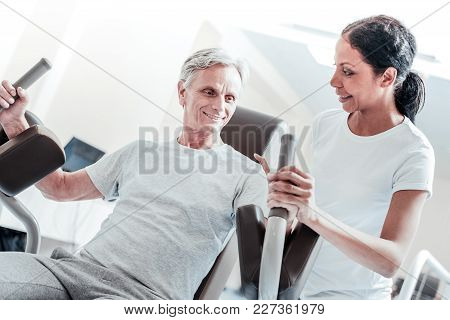 Training Device. Inspired Old Crippled Grey-haired Man Smiling And Exercising On A Training Device A