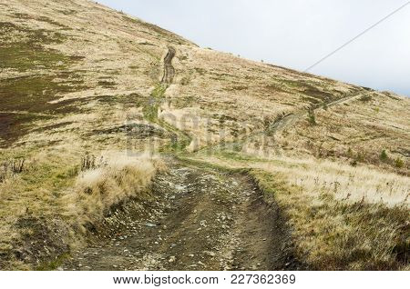 Fork In The Road. Roads That Diverge. Mountain Trails. Clouds