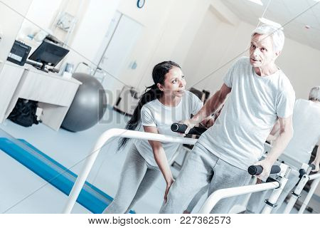 That Is Right. Determined Old Wrinkled Grey-haired Man Exercising On A Training Device While A Young