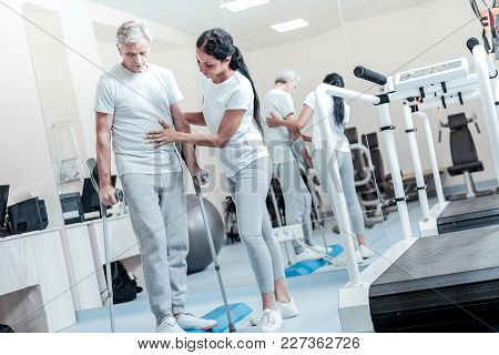 Succeeding In Training. Attractive Happy Dark-haired Woman Helping A Concentrated Old Grey-haired Ma