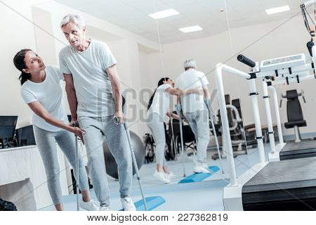 Assistance. Attractive Joyful Dark-haired Woman Helping A Concentrated Old Grey-haired Man Walk And