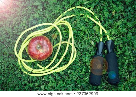 Skipping Rope And Red Apple On Grass