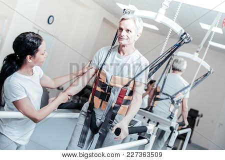 Learning To Walk. Vigorous Old Grey-haired Man Smiling And Exercising On A Training Device And Learn