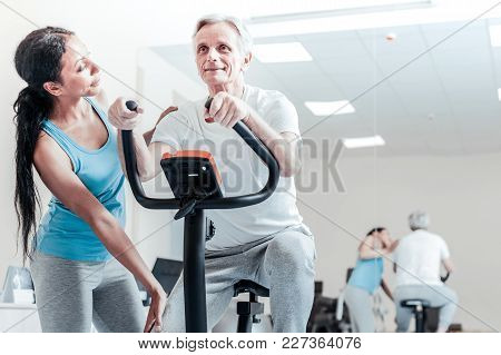 Active Lifestyle. Alert Smiling Aged Grey-haired Man Exercising On A Training Device While A Beautif