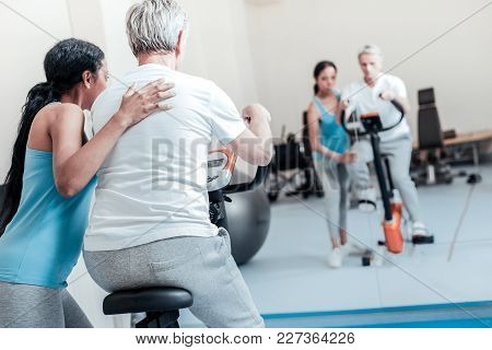 Keep Doing. Old Grey-haired Man Dressed In White Shirt Exercising On A Training Device While A Young