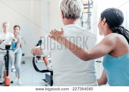 Exercising Together. Old Grey-haired Man Dressed In White Shirt Exercising On A Training Device Whil