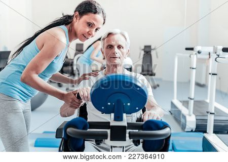 I Support You. Determined Old Grey-haired Man Exercising On A Training Device While A Smiling Young