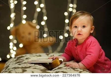 Portrait Of A Little Girl In A Pink Dress In The Studio. Lights Backgrounds