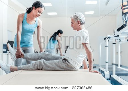 Raising Legs. Serious Old Grey-haired Crippled Man Sitting On Bed While A Concentrated Young Dark-ha