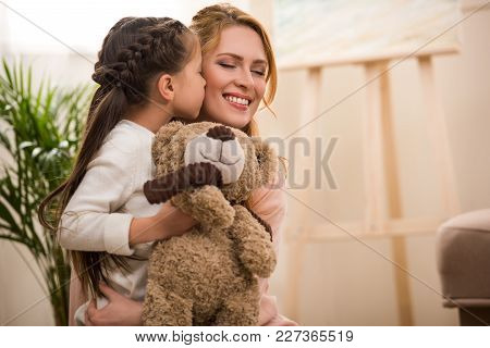 Cute Little Child Holding Teddy Bear And Kissing Happy Mother At Home