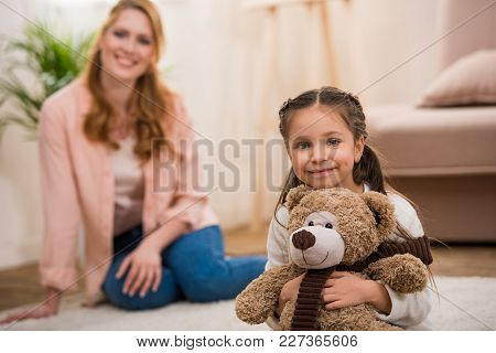 Adorable Little Child Holding Teddy Bear And Smiling At Camera While Mother Sitting Behind At Home