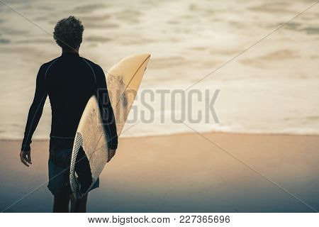 Image Of Surfer Walking On Beach To Blue Ocean For Big Wave In Bali, Indonesia. Surfer At Surf Spot.