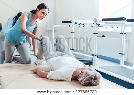 Helping Recover. Concentrated Old Grey-haired Crippled Man Lying On Bed While An Alert Young Dark-ha