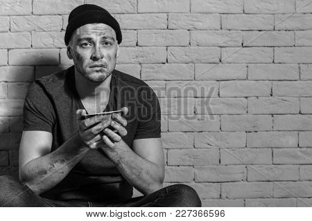 Hungry poor man holding bowl with piece of bread while sitting near brick wall