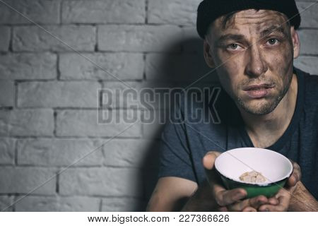 Homeless poor man holding bowl with piece of bread near brick wall