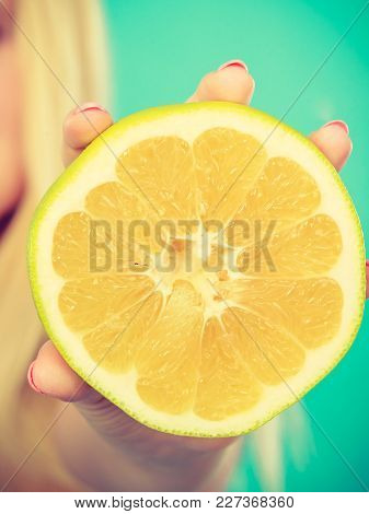 Half Of Yellow Grapefruit Citrus Fruit In Female Hand Closeup, On Blue Green. Healthy Diet Weight Lo