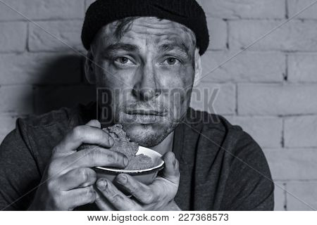 Hungry poor man holding bowl with piece of bread against brick wall