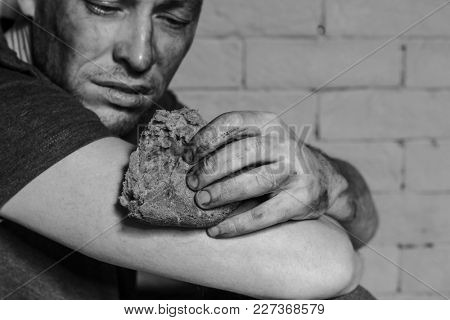 Hungry poor man with piece of bread near brick wall
