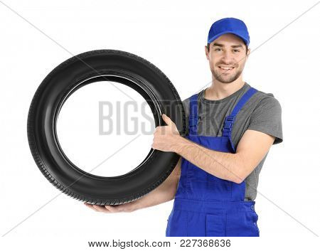 Young mechanic in uniform with car tire on white background