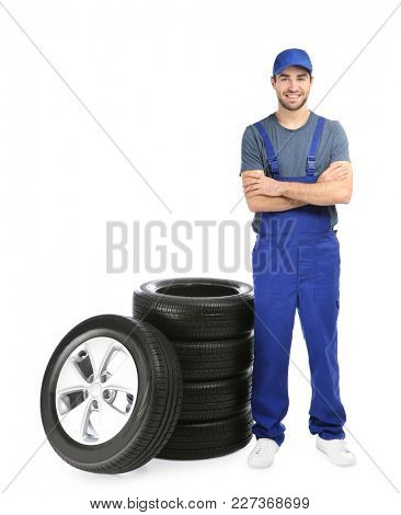 Young mechanic in uniform with car tires on white background