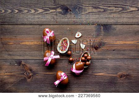 Chocolate Easter Eggs On Dark Wooden Background Top View.