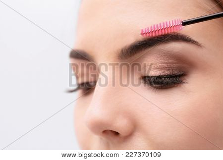 Young woman correcting shape of eyebrows, closeup