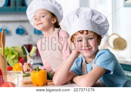 Adorable Siblings In Chef Hats And Aprons Smiling At Camera While Cooking In Kitchen