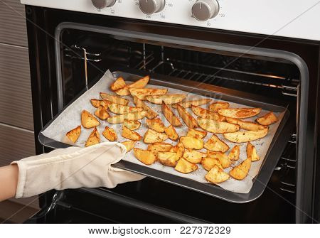 Woman taking baking sheet with delicious potatoes from oven